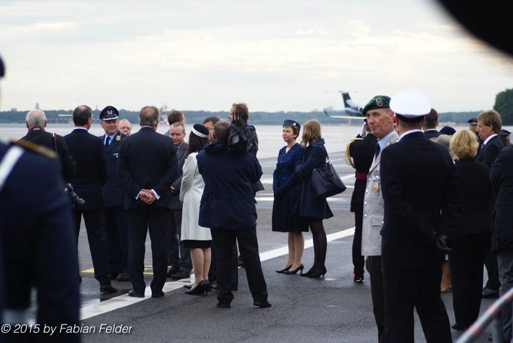 Am Flughafen wartet eine große Delegation aus Gesellschaft, Politik und Vertretern beider Länder, um die Queen und den Herzog von Edinburgh in Empfang zu nehmen.
